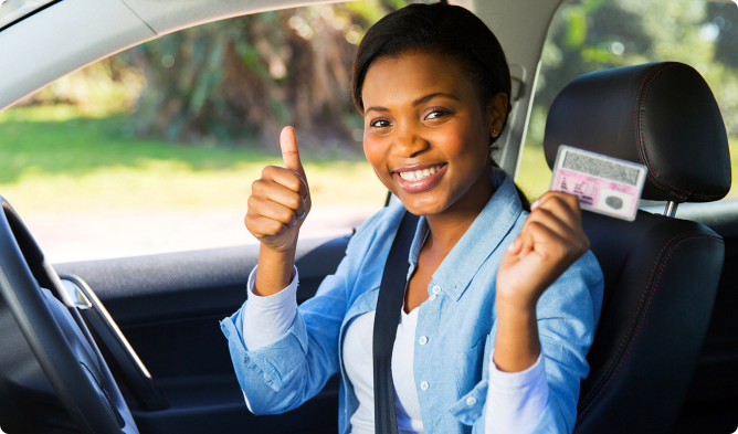 A student driver raising her license while doing a thumbs-up sign