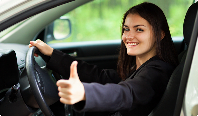 A female student driver doing a thumbs-up sign