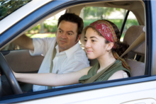 A teen student driver with her driving instructor
